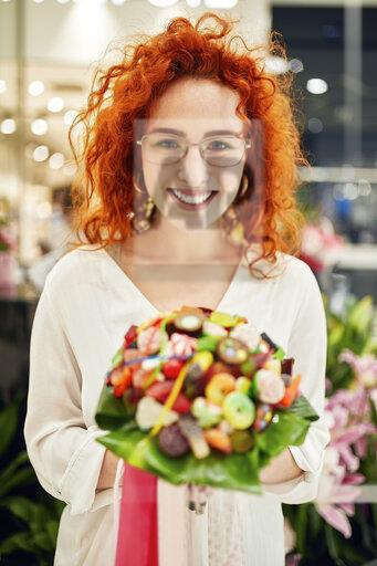 Portrait of smiling woman holding candy bouquet in a shop