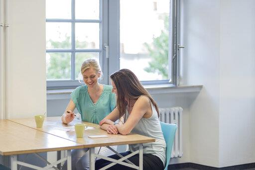 Two smiling businesswomen working on document in office