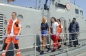 In this photo taken Aug. 19, 2018, a woman who identified herself as Kay from England, center, is escorted by rescuers from a Croatian Coast Guard vessel in the port in Pula, Croatia. A British woman was rescued Sunday after falling from a cruise ship and spending 10 hours in the Adriatic Sea at night, Croatia's coast guard said. (AP Photo)