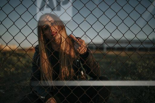 Portrait of young woman sitting behind wire mesh fence giving the finger
