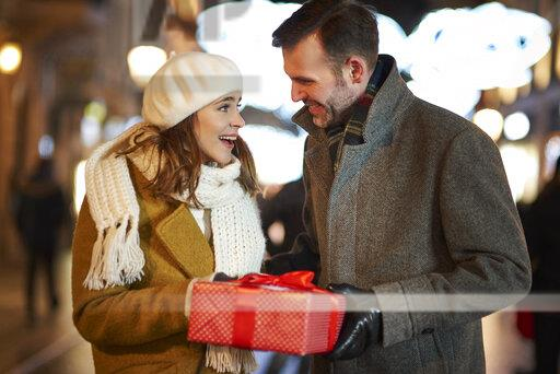 Man giving gift to his amazed girlfriend