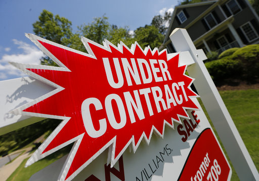 FILE - In this Tuesday, May 16, 2017, file photo, a sign advertises that an existing home for sale is under contract in Roswell, Ga. Surging stock prices and steady increases in home values powered American household wealth to $96.9 trillion in the fall of 2017, though the gains aren't widely shared. (AP Photo/John Bazemore, File)