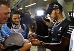 Mercedes driver Lewis Hamilton of Britain signs autographs for fans after the Emirates Formula One Grand Prix at the Yas Marina racetrack in Abu Dhabi, United Arab Emirates, Sunday, Nov. 26, 2017. . (AP Photo/Hassan Ammar)