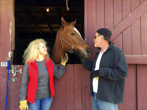 Brian Bromberg, 57, and his Wendy Frank, 51, pose with one of the horses they rescued from their Ojai, Calif., home at the Ventura County Fairgrounds evacuation center in Ventura, Calif.,Thursday, Dec. 7, 2017. They share a harrowing tale. They not only evacuated their Upper Ojai home on Tuesday afternoon, after they watched every property around theirs burn up and were putting out hot spots by hand, but also had to evacuate their horses again Wednesday night from where they were being boarded in Ojai. Their property is safe for now and they're calling their survival and that of their beloved horses a miracle. (AP Photo/Amanda Lee Myers)