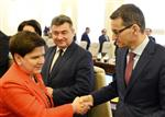 In this Dec. 5, 2017 photo Poland's Prime Minister, Beata Szydlo, left, shakes hands with Finance Minister, Mateusz Morawiecki, right, prior to a government meeting in Warsaw, Poland, Tuesday, Dec. 5, 2017. Poland's conservative ruling party says Szydlo has resigned and will be replaced by Morawiecki. (AP Photo/Alik Keplicz)