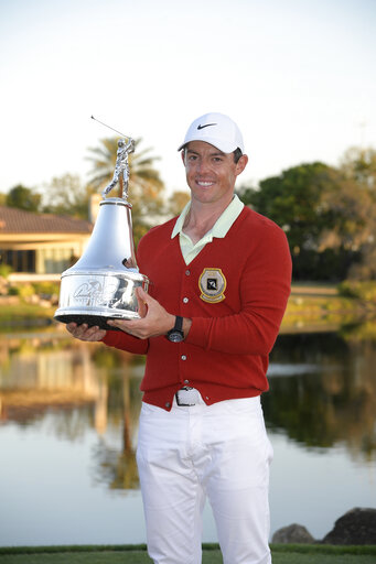 ... Rory McIlroy, of Northern Ireland, poses with the championship trophy after winning the Arnold Palmer Invitational golf tournament in Orlando, Fla.