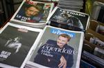 French newspapers with portraits of late rock star Johnny Hallyday are displayed in a street news stand of Paris, France, Thursday, Dec. 7, 2017. Johnny Hallyday, France's biggest rock star for more than half a century and an icon who packed sports stadiums and all but lit up the Eiffel Tower with his high-energy concerts at the foot of the Paris landmark, died early Wednesday. He was 74. (AP Photo/Francois Mori)