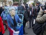 French fan Andre Duval holds a portrait of Johnny Hallyday outside his house in Marnes-la-Coquette, outside Paris, Wednesday, Dec.6, 2017. Johnny Hallyday, France's biggest rock star for more than half a century and an icon who packed sports stadiums and all but lit up the Eiffel Tower with his pumping pelvis and high-voltage tunes, has died. He was 74. (AP Photo/Michel Euler)
