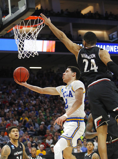 abf73c0296c UCLA guard Lonzo Ball, left, goes to the basket against Cincinnati forward  Kyle Washington during the first half of a second-round game of the NCAA  men's ...