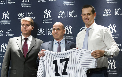 New York Yankees owner Hal Steinbrenner, left, general manager Brian Cashman, center, and Aaron Boone, pose for photographers during a news conference introducing  Boone as the baseball team's new manager, Wednesday, Dec. 6, 2017, at Yankee stadium in New York. (AP Photo/Mary Altaffer)
