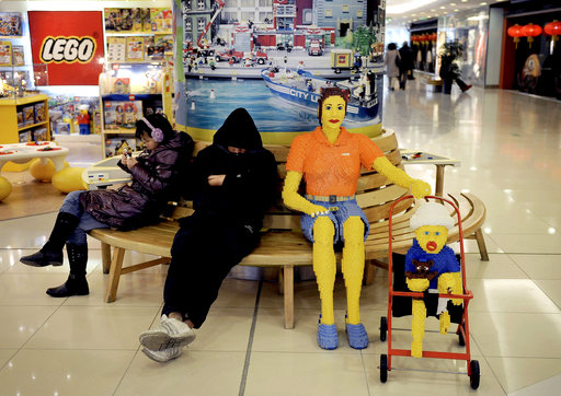 FILE - In this  Jan. 12, 2010, file photo, a man takes a nap next to a life size human figure built with Lego toy blocks displayed at a shopping mall in Beijing. Danish toy maker Lego says Thursday Dec. 7, 2017 that it has won major legal victory in China, where a court ruled in its favor in a copyright case against companies making knockoffs of its famous colored bricks. (AP Photo/Andy Wong, File)