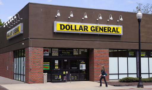 FILE - In this Wednesday, May 18, 2016, file photo, a woman walks near a Dollar General store in Methuen, Mass. On Thursday, Dec. 7, 2017, Dollar General Corp. reported earnings that topped Wall Street's expectations. (AP Photo/Charles Krupa, File)