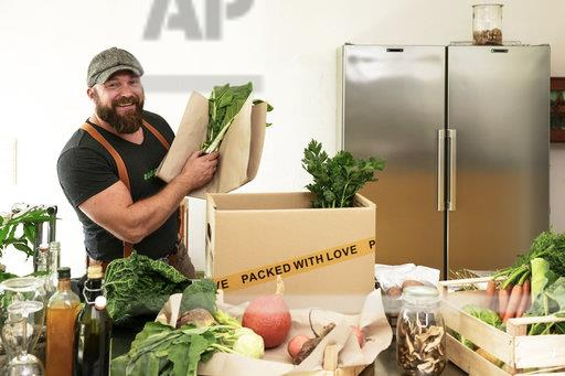 Mature man with delivery service packing organic vegetables