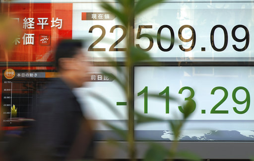A man walks past an electronic stock board showing Japan's Nikkei 225 index at a securities firm in Tokyo Wednesday, Dec. 6, 2017. Shares in Asia fell Wednesday after another afternoon fizzle for stocks that left the Standard & Poor's 500 index with its third straight loss. (AP Photo/Eugene Hoshiko)