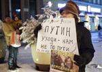A protester stands in a one-person picket, holding a poster reading 'Putin go away-we do not follow your path!' in St.Petersburg, Russia, Wednesday, Dec. 6, 2017.  Russian President Vladimir Putin on Wednesday declared his intention to seek re-election next March, a vote he appears certain to win. (AP Photo/Dmitri Lovetsky)