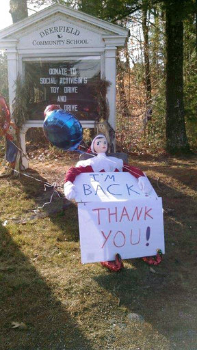 In this photo provided by Cindy McHugh, Zippy, the beloved elf on a shelf for the town of Deerfield, N.H., sits in front of the Deerfield Community School on Wednesday, Dec. 6, 2017. Zippy, who appears throughout the town during the holiday season, was taken on Monday afternoon and mysteriously reappeared Wednesday morning in front of a resident's home. (Cindy McHugh via AP)