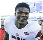 FILE - In this Nov. 25, 2017, file photo, Louisville quarterback Lamar Jackson smiles as he leaves the field after his team defeated Kentucky 44-17 in an NCAA college football game, in Lexington, Ky. Jackson was selected to the AP All-Conference ACC team announced Tuesday, Dec. 5, 2017. (AP Photo/David Stephenson, File)