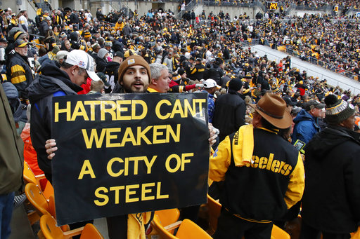 89681aadcf7 A Pittsburgh Steelers fan holds a sign honoring the victims of a deadly  shooting spree at a synagogue on Saturday during the second half of an NFL  football ...